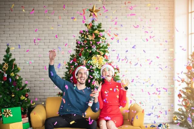 A man and woman sit in front of a Christmas tree celebrating plumbing tips